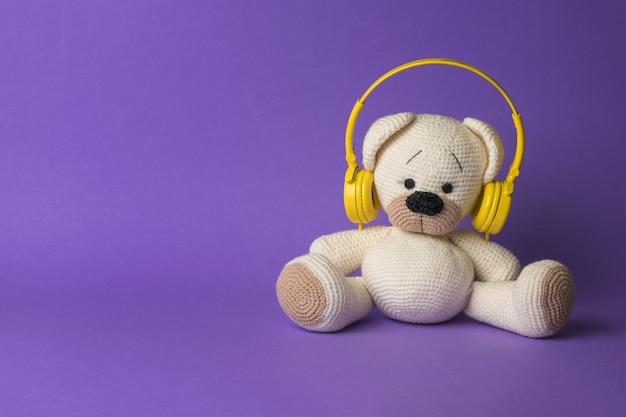 Ein weißer strickbär mit gelben kopfhörern auf violettem hintergrund. das konzept der liebe zur musik.