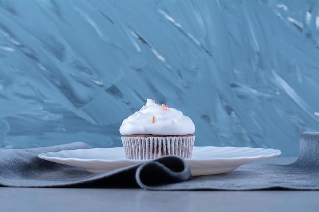 Ein weißer teller eines cremigen cupcakes mit bunten streuseln.