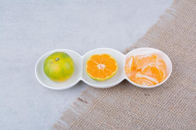 Ein weißer teller geschälter mandarinen auf sackleinen. foto in hoher qualität