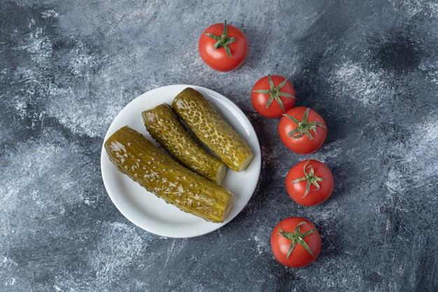 Ein weißer teller mit eingelegten gurken mit tomaten.