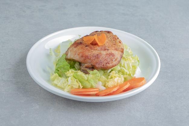 Ein weißer teller mit gebratenem hühnerfleisch und geschnittener karotte.