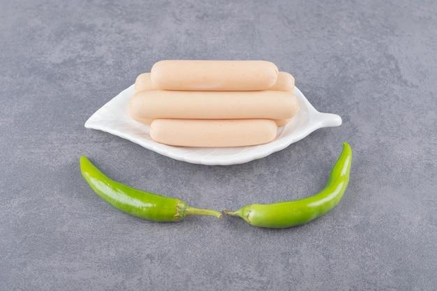 Ein weißer teller mit gekochten würstchen und chilischoten