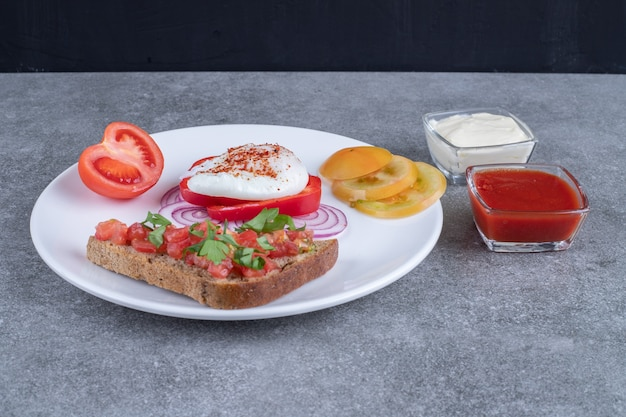 Ein weißer teller mit geschnittenem gemüse und gekochtem ei