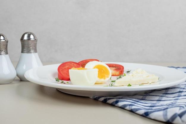 Ein weißer teller mit geschnittenen tomaten und gekochtem ei.
