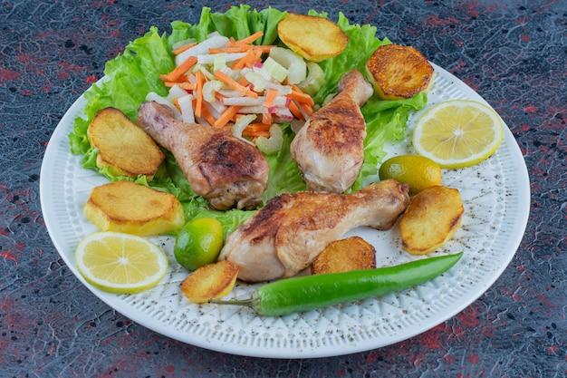 Ein weißer teller mit hühnerfleisch mit geschnittenem gemüse.
