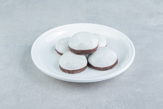 Ein weißer teller mit lebkuchenplätzchen mit puderzucker.