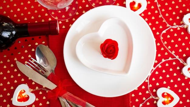 Ein weißer teller mit messer und gabel auf einem leuchtend roten mit weinflasche. herzförmiger weißer teller. valentinstag. der blick von oben.