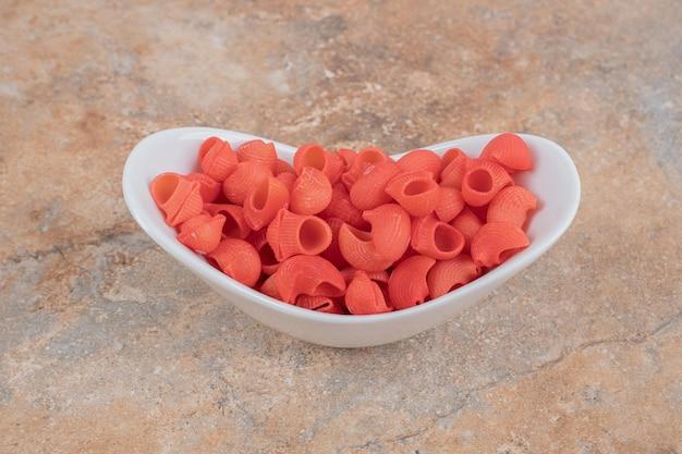 Ein weißer teller mit roten, ungekochten makkaroni auf marmorraum.
