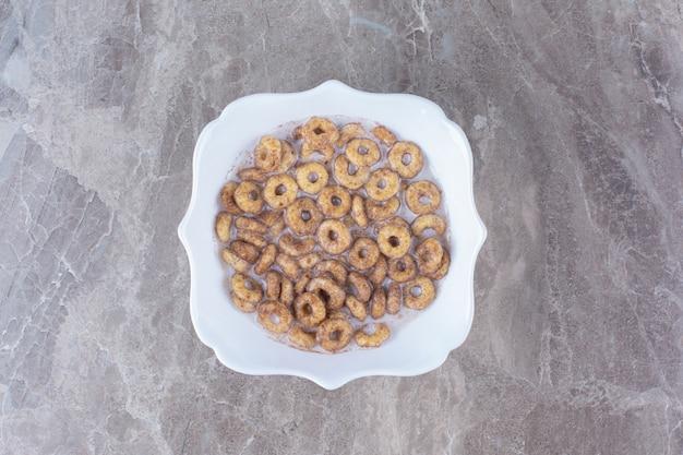 Ein weißer teller mit schokoladen-getreideringen mit milch auf grauem tisch.
