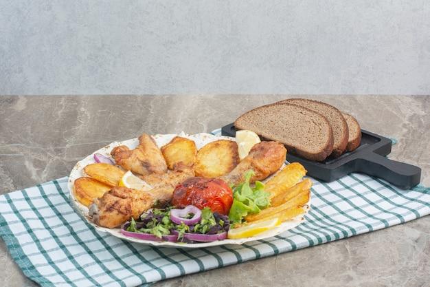 Ein weißer teller voller brathähnchen und kartoffeln mit schwarzbrot.