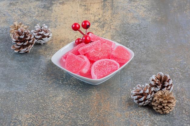 Ein weißer teller voller roter fruchtgelee-bonbons und tannenzapfen. hochwertiges foto