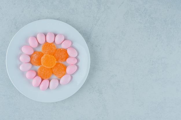 Ein weißer teller voller süßer orangenmarmeladen und rosa bonbons. foto in hoher qualität