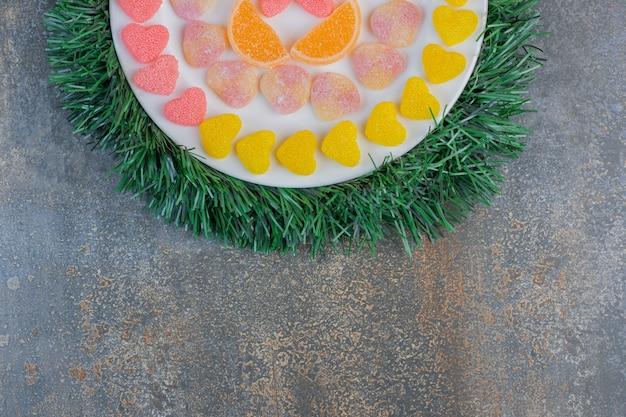 Ein weißer teller voller verschiedener saftiger bunter geleebonbons. hochwertiges foto