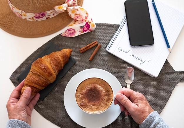 Ein weißer tisch mit einem süßen frühstück. hausgemachter cappuccino mit zimtpulver und einem frischen croissant. smartphone – alter lifestyle und neue technik