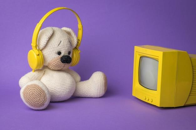 Ein weißes bärenjunges mit kopfhörern vor dem fernseher auf violettem hintergrund.