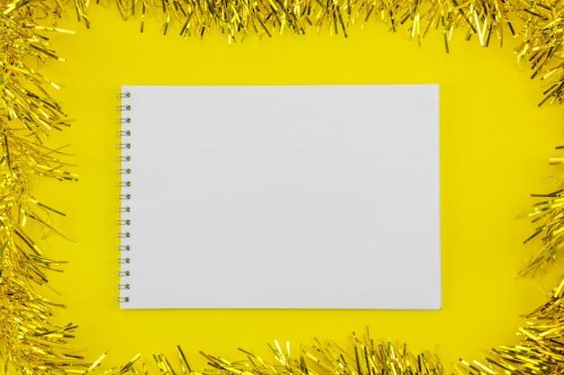 Ein weißes blatt papier auf einem gelben weihnachtshintergrund mit lametta.