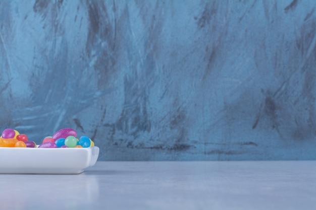 Ein weißes brett voller bunter bohnenbonbons auf grauem tisch.