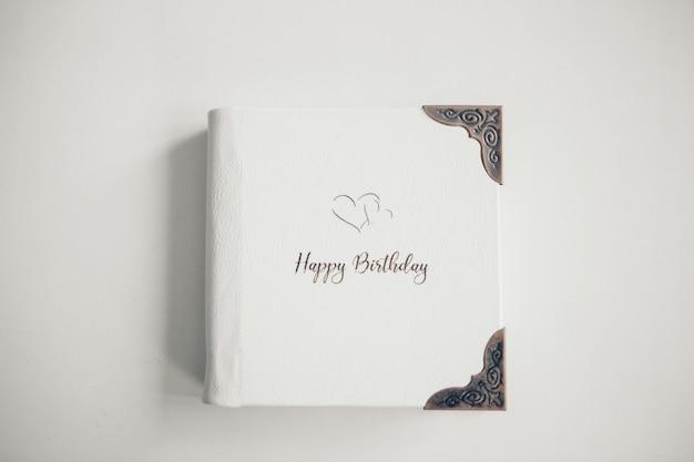 Ein weißes buch, eingewickelt in leder auf einem weißen hintergrund. fotoalbum mit metallrahmen. grußkarte