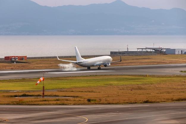 Ein weißes flugzeug landet am flughafen