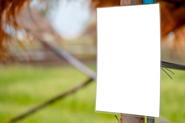Ein weißes mockup-schild, das auf einer holzstange montiert ist.
