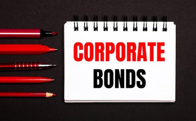 Ein weißes notizbuch mit dem text corporate bonds neben roten kugelschreibern, bleistiften und markern auf schwarzem hintergrund.
