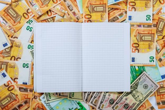 Ein weißes notizbuch mit leeren seiten lag auf einem satz banknoten von 100 euro, 50 euro und 100 dollar.