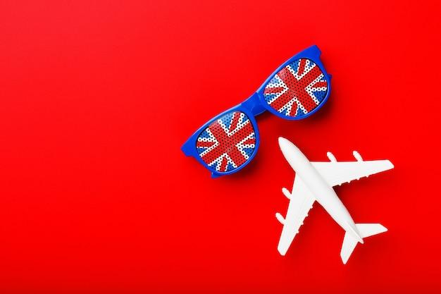 Ein weißes passagierflugzeug fliegt in sonnenbrille mit der flagge des vereinigten königreichs ,.