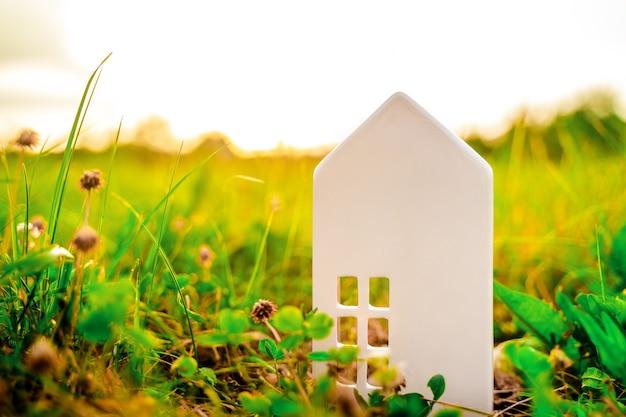 Ein weißes spielzeughaus im gras das konzept eines umweltfreundlichen lebensstils eco