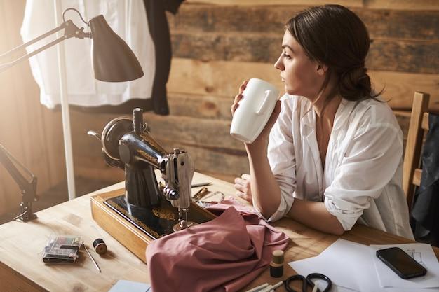 Ein weiterer tag in der werkstatt ging zu ende. verträumter nachdenklicher weiblicher abwasserkanal, der beiseite schaut, während er nahe nähmaschine sitzt, tee trinkt und pause von der arbeit hat. designer lädt sich mit heißem kaffee auf