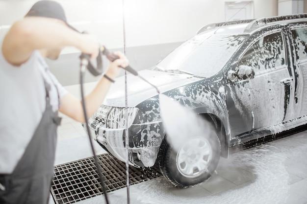 Ein weiteres bild eines mannes, der im zimmer steht und das rad und den reifen des autos wäscht. dafür benutzt er einen flexiblen schlauch mit wasser. er konzentriert sich auf den prozess.
