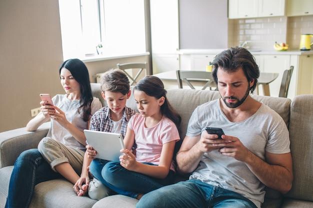 Ein weiteres bild von der familie, die zusammen sitzt. eltern halten hpones in händen und schauen es an. mädchen hat tablette. sie und ihr bruder schauen es sich an.