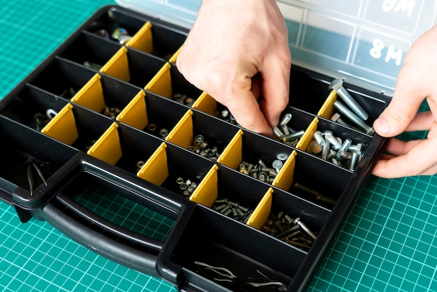 Ein werkzeugkasten mit zellen mit schrauben, dübeln, nägeln, bolzen und anderen werkzeugen in der werkstatt