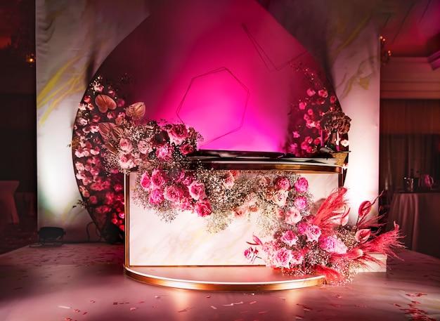 Ein willkommensbereich mit einem tisch für eine hochzeit oder ein jubiläum, dekoriert von einem floristen mit frischen blumen