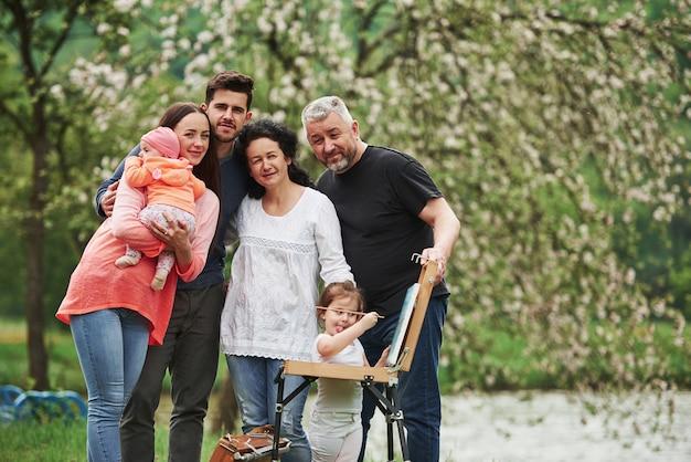 Ein wochenende zusammen verbringen. familie haben gute zeit in der parklandschaft. junger maler, der das zeichnen lehrt