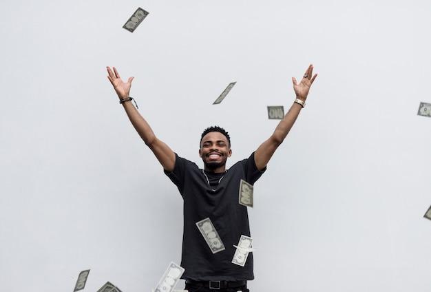 Ein wohlhabender afrikanischer mann, der sein geld wegwirft