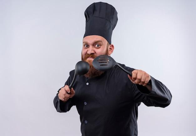Ein wütender bärtiger kochmann in der schwarzen uniform, die schwarze kelle und geschlitzten löffel auf einer weißen wand erhebt