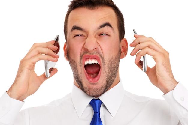 Ein wütender geschäftsmann, der gleichzeitig auf zwei telefonen auf weißem hintergrund spricht Premium Fotos