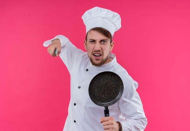 Ein wütender junger bärtiger kochmann in der weißen uniform, die kochmütze hält, die bratpfanne mit messer hält, während mit negativem ausdruck auf einer rosa wand schaut