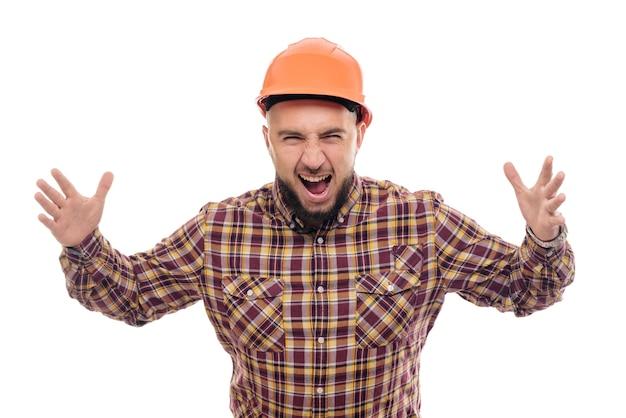Ein wütender und nervöser arbeiter in einem orangefarbenen helm telefoniert laut und schreit ins telefon. isolierter weißer hintergrund