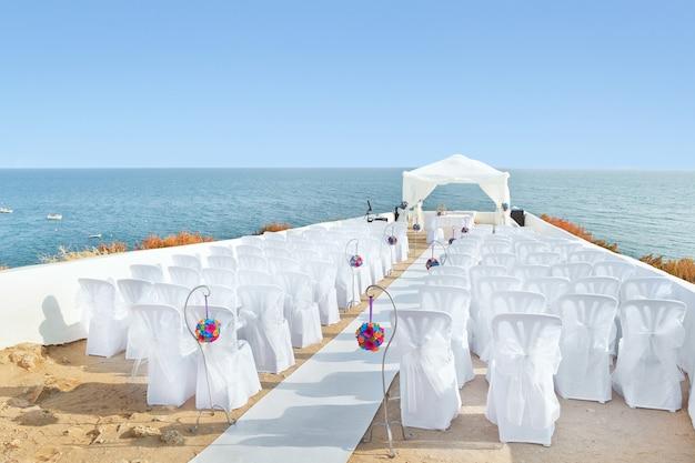 Ein wunderbarer ort in den dekorationen und blumen für die hochzeitszeremonie. mit weißen stühlen am meer.