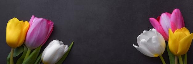 Ein wunderschöner heller strauß mehrfarbiger tulpen in nahaufnahme gegen eine dunkelgraue stuckwand.