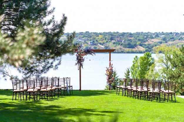 Ein wunderschöner ort für eine hochzeitszeremonie unter freiem himmel. hochzeitsbogen und reihen von gaststühlen auf einem grünen rasen mit blick auf den fluss