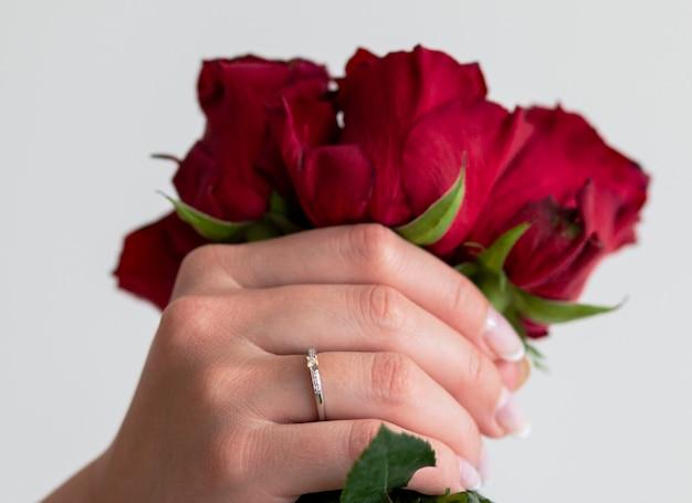 Ein wunderschöner stilvoller ring mit diamanten am finger und wunderschönen rosen