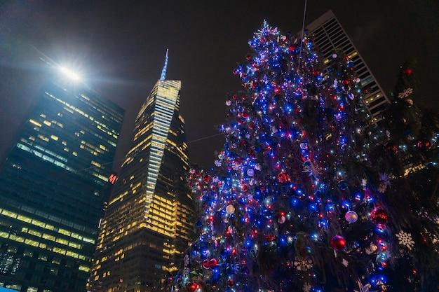 Ein wunderschöner weihnachtsbaum, der nachts mit vielen roten und blauen lichtern beleuchtet wird