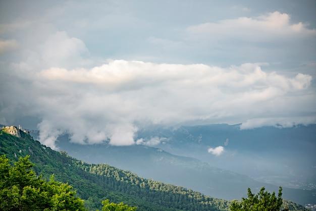 Ein wunderschönes dramatisches bergpanorama mit schweren nebelwolken