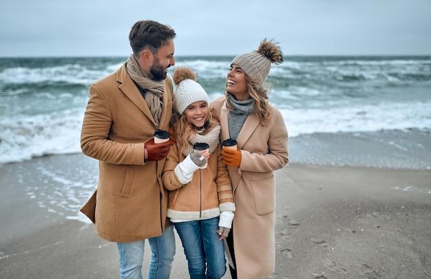 Ein wunderschönes ehepaar und seine charmante tochter gehen an die küste und trinken kaffee in warmen kleidern.
