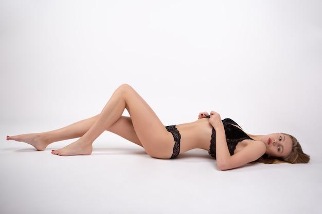 Ein wunderschönes sexy blondes model mit einem perfekten körper liegt in schwarzer spitzenunterwäsche