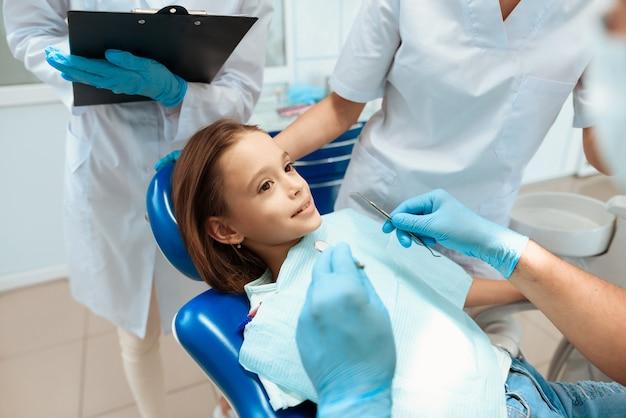 Ein zahnarzt bereitet vor sich, die zähne eines kleinen mädchens zu behandeln.