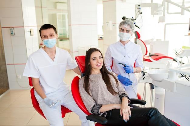 Ein zahnarzt mit einer assistentin heilt einem schönen mädchen die zähne.