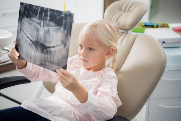 Ein zahnarzt zeigt einem kleinen mädchen eine röntgenaufnahme von echten zähnen